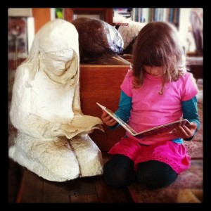 my daughter age 7 reading beside a papier mache portrait my mother made of me at the same age - we never got a perfect photo of me with the statue because by the time she had completed it, I had grown several inches!