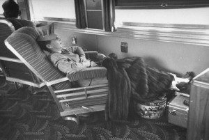 A woman sleeping on a lounge chair in the observation lounge car.